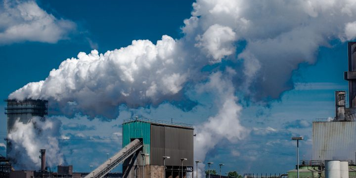 Image of a factory with smoke bellowing from a smokestack in the background.